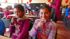 students in smiling in class in poverty stricken part of peru