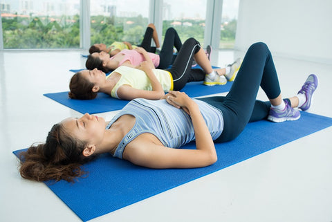 Women performing breathing exercise on yoga mat