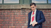 Lesovs Red and Gray Striped Tie on man by bricks