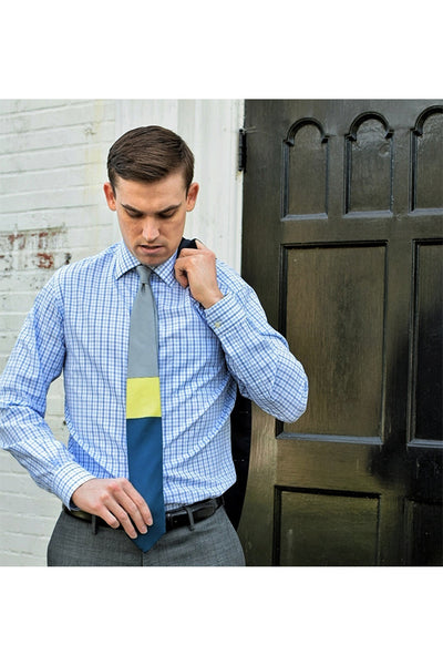 Gray Yellow Blue Tie in Front of Wall and Door