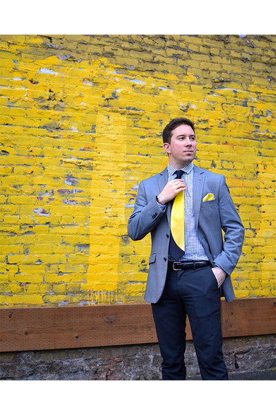 Lesovs Black and Yellow Eclipse Tie in front of yellow wall