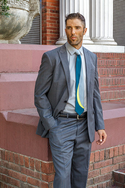 Lesovs Gray Curves Silk Tie on man in front of bricks