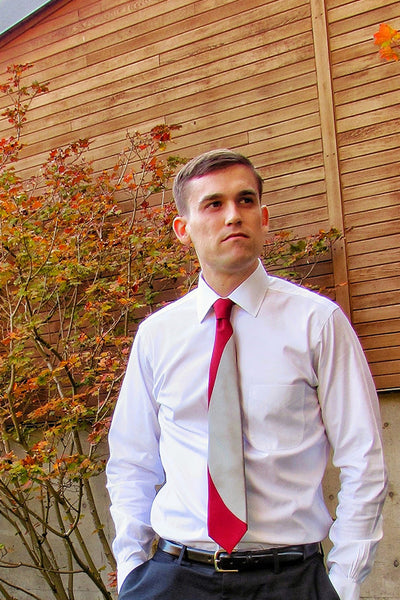 Lesovs Red and Gray Eclipse Designer Silk Tie in front of building and trees