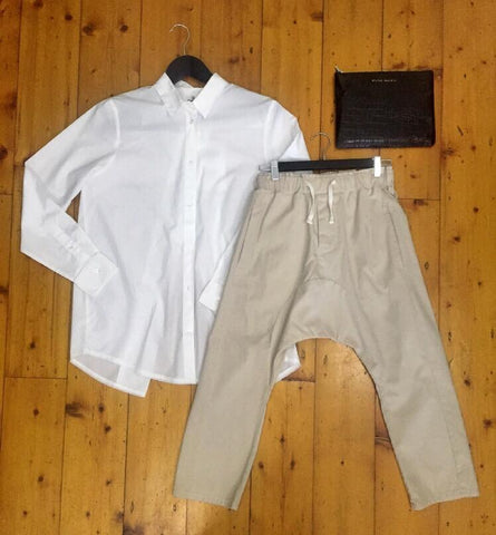 White button top, beige pants, black clutch