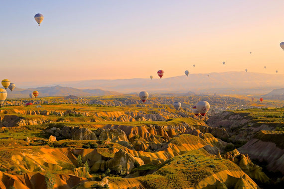 Air ballons around hills Canvas