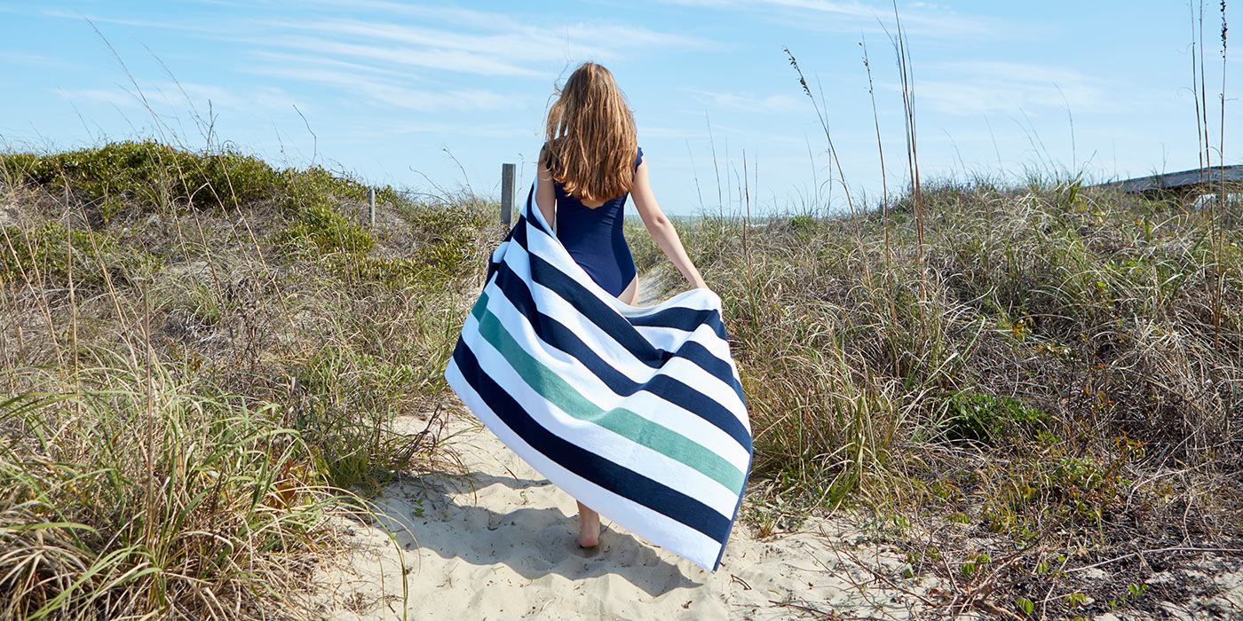Woman on sand dunes wrapped in navy and green luxury cabana beach towel.