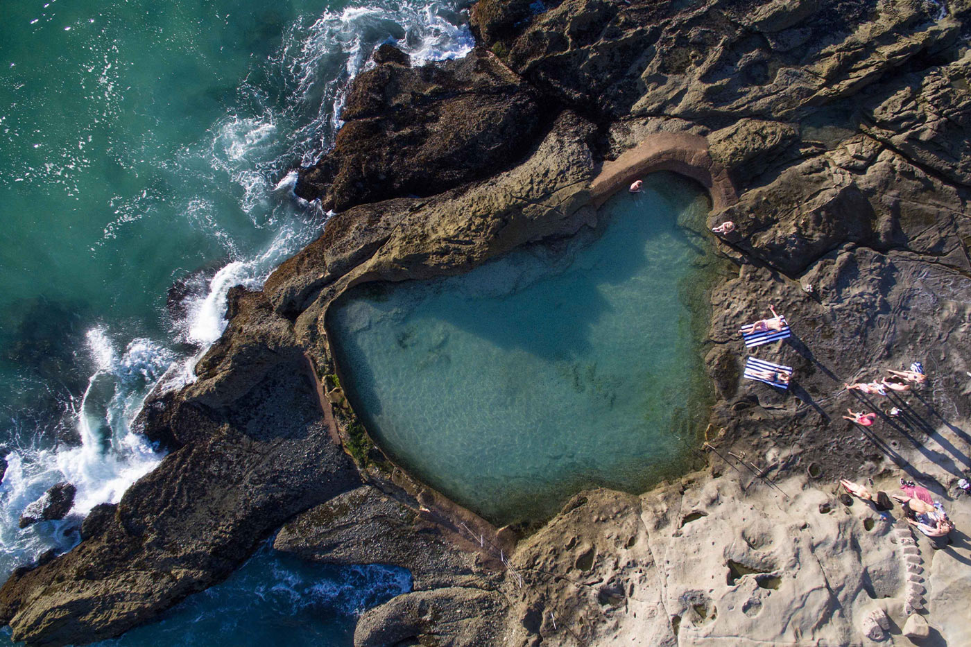 Aerial bird's eye view of Laguna Beach with friends sitting on cabana towels.
