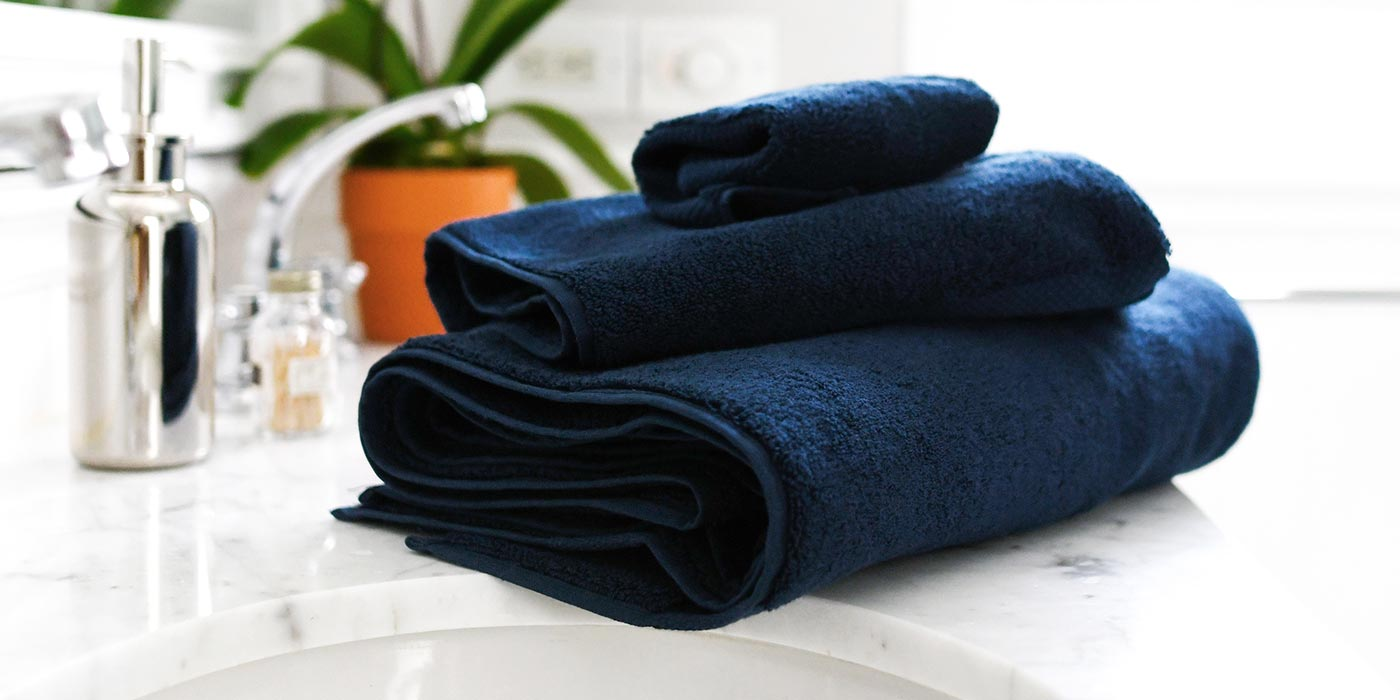 Stack of navy blue Supima cotton bath towel, hand towel, and wash cloth.
