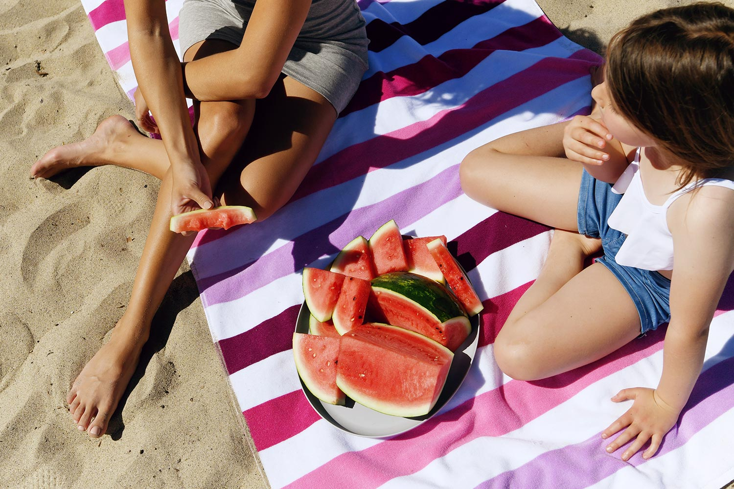 Woman and girl sitting on a pink and purple cabana beach towel eating watermelon on a sandy beach.