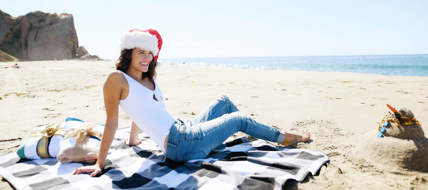 Woman in a santa hat sitting on the beach on black, gray, and white picnic blanket.