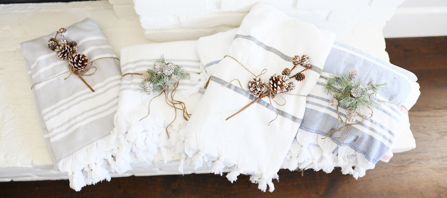 Oversized white, gray, and blue Turkish towels wrapped as beautiful holiday gifts.