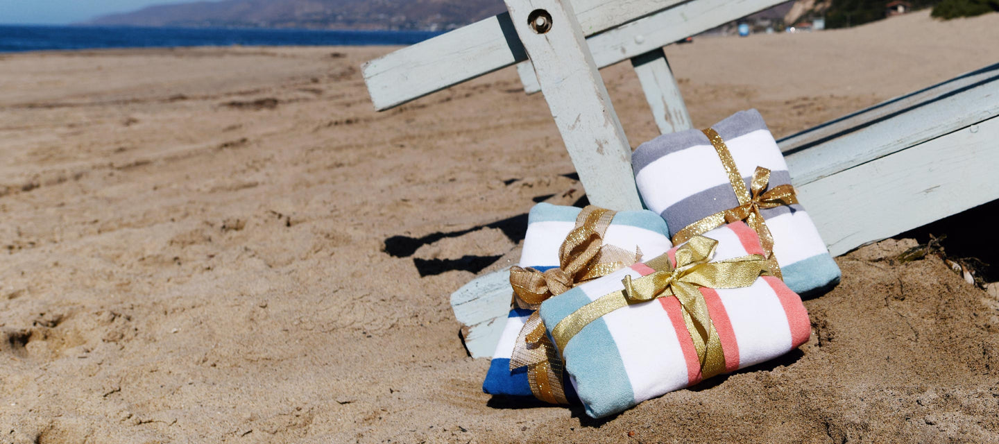 Cabana beach towels on the beach wrapped as Christmas gifts. The towel colors are coral, teal, gray, and blue.