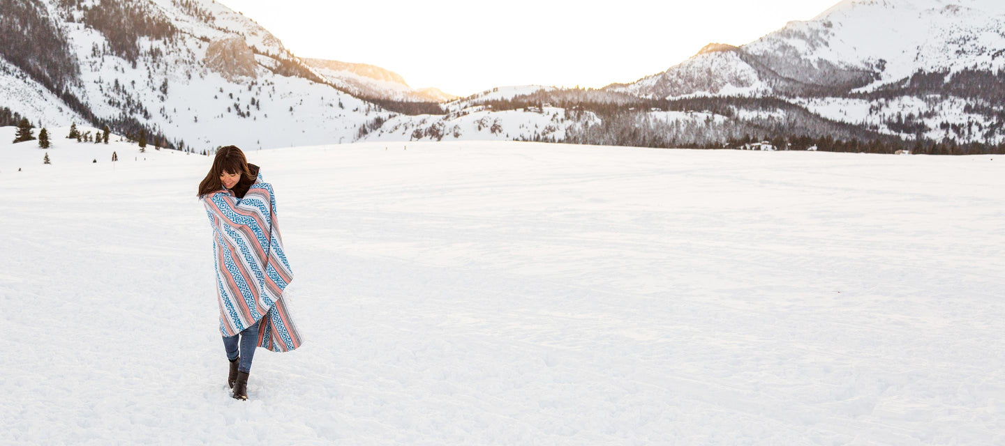 Blush pink, gray, and blue cozy Mexican blanket wrapped around a woman standing in winter landscape surrounded by snowy mountains