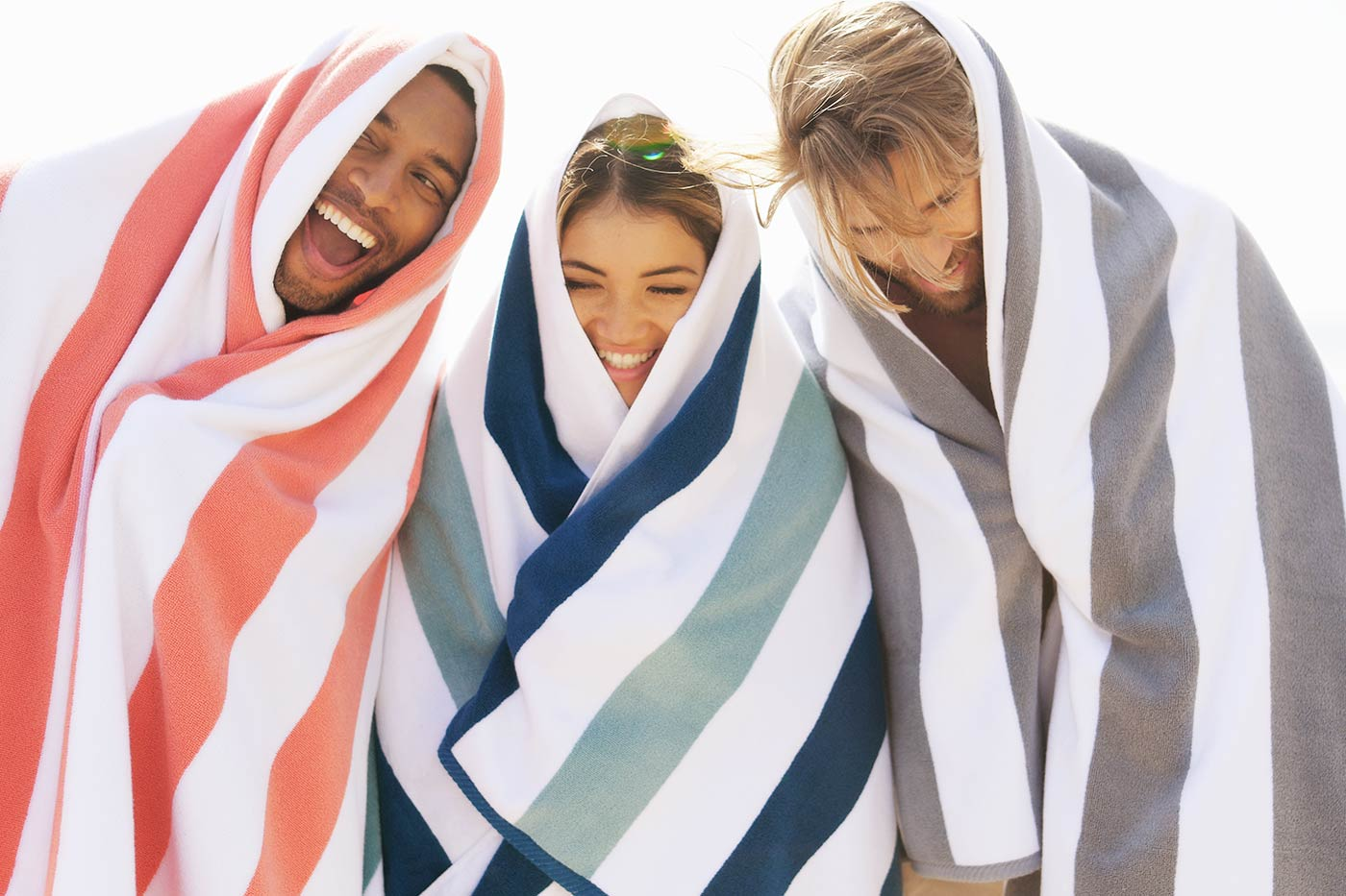 Three friends wrapped in oversized luxury cabana beach towels in coral pink, blue, teal, and gray.
