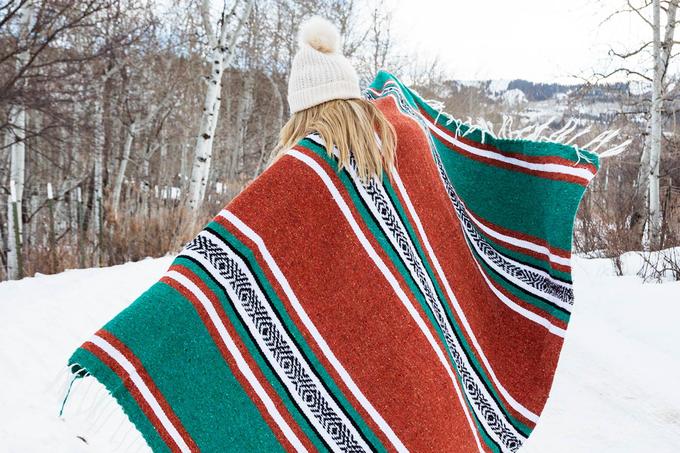 Green, burnt orange, red Mexican blanket wrapped around a woman against a winter landscape