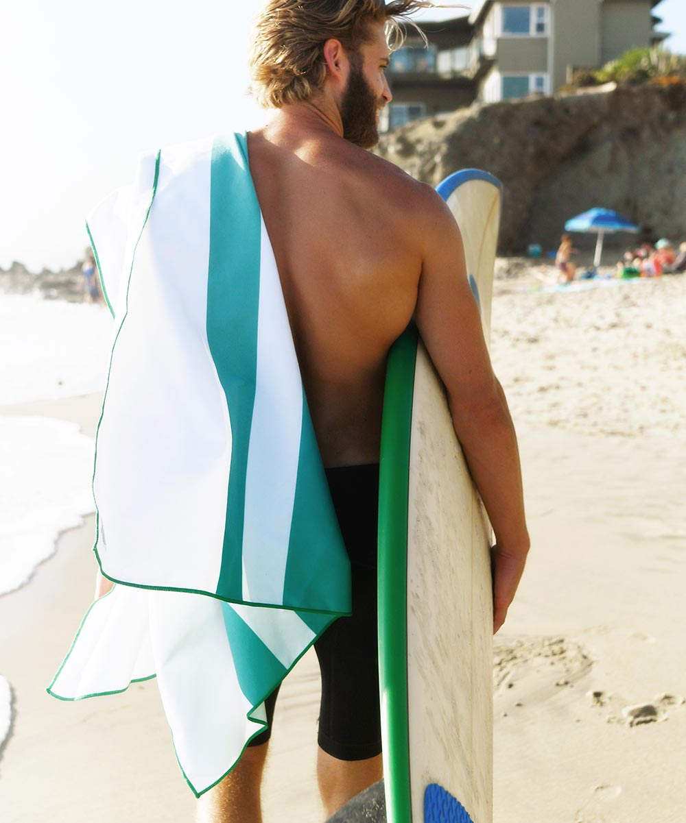 Man carrying a surf board holding turquoise, green, aqua, microfiber beach towel.