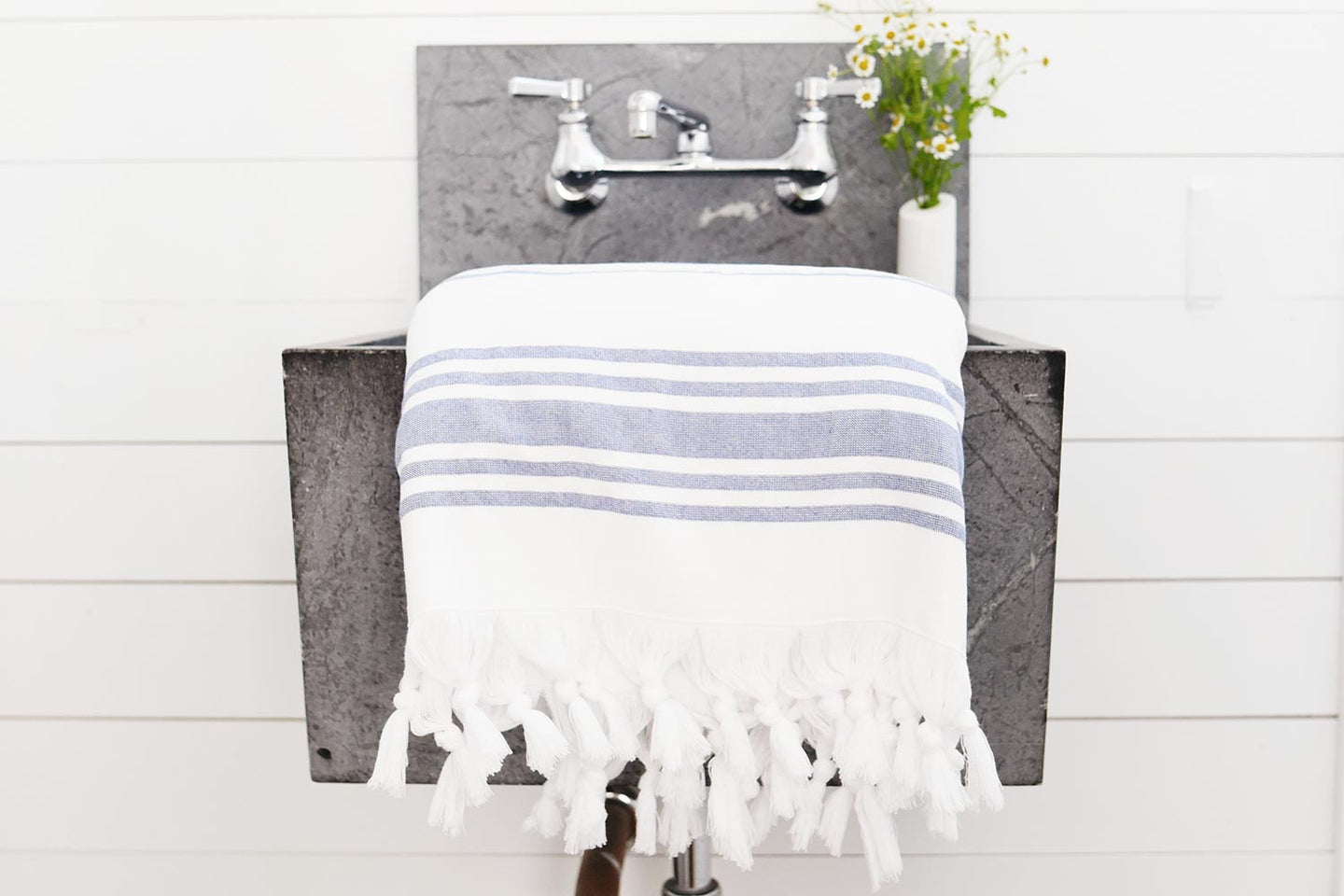 White and denim blue luxury Turkish towel draped in bathroom over modern sink.