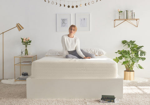 Blonde woman sitting on a white memory foam gel mattress in a white themed room