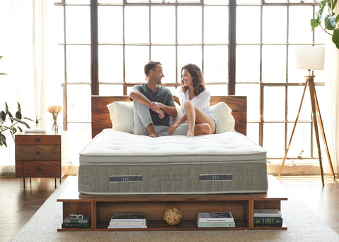 couple sitting on an all natural hybrid latex mattress made from sustainable materials