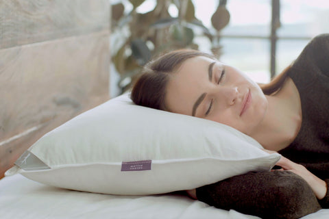 brunette woman resting her head on a natural latex & kapok pillow