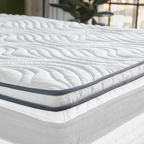 Memory foam mattress topper on a clean white mattress