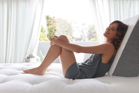 Woman sitting on a bed and leaning against a gel memory foam wedge pillow