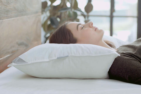 Brunette woman resting her head on a Gel Memory Foam Pillow