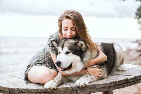 CocoTherapy woman hugging black and white siberian husky