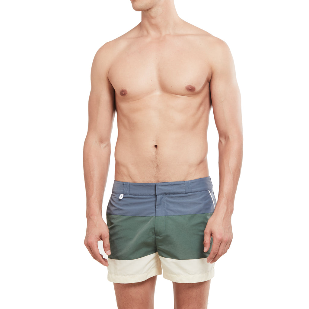 Blue, green, and white bathing trunks on model