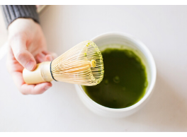 hand holding bamboo whisk over bowl of matcha