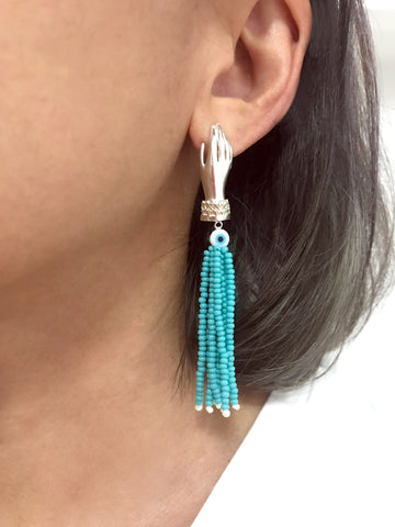 Hands with Turquoise tassel and Eye earrings