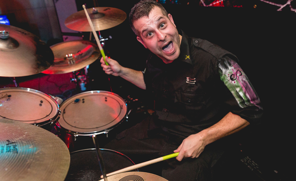 Drummer posing during live performance with drums
