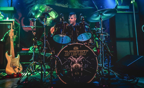 Drummer on stage with drumset and music instruments