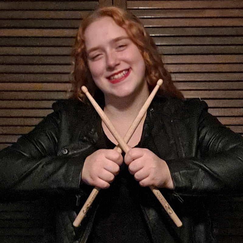Drummer Anastasia McCoy poses with Scorpion Percussion drumsticks behind his drumkit
