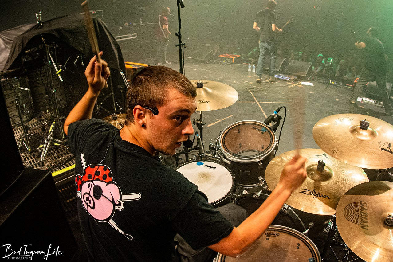 Drummer Alex Raser poses with Scorpion Percussion drumsticks behind his drumkit