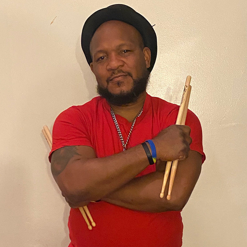 Drummer Aaron Fennell poses with Scorpion Percussion drumsticks behind his drumkit