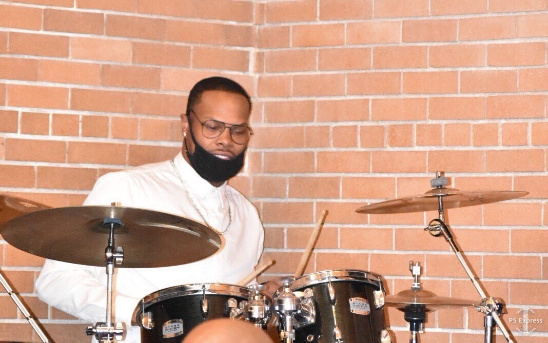 Drummer Justin McGee poses with Scorpion Percussion drumsticks behind his drumkit