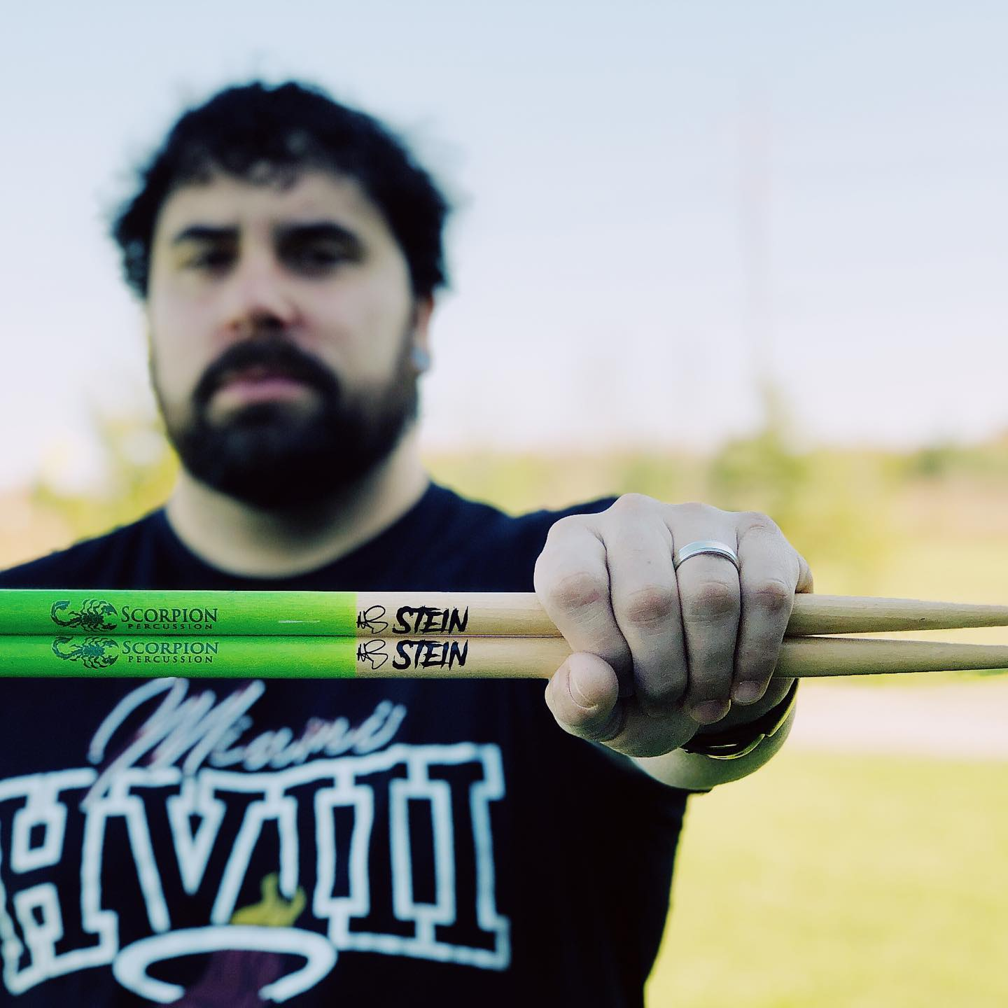 Drummer Matt Stein poses with Scorpion Percussion drumsticks behind his drumkit
