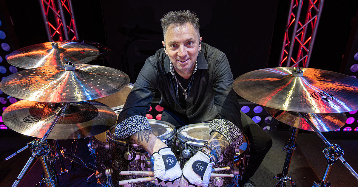 Drummer Craig Dischinger poses with Scorpion Percussion drumsticks behind his drumkit