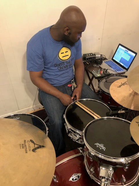Drummer Armund Eison poses with Scorpion Percussion drumsticks behind his drumkit