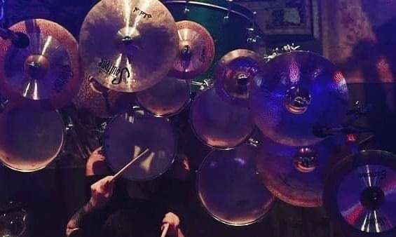 Drummer Nicholas Talarico poses with Scorpion Percussion drumsticks behind his drumkit
