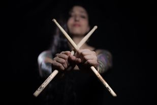 Drummer Carolina Perez poses with Scorpion Percussion drumsticks behind his drumkit