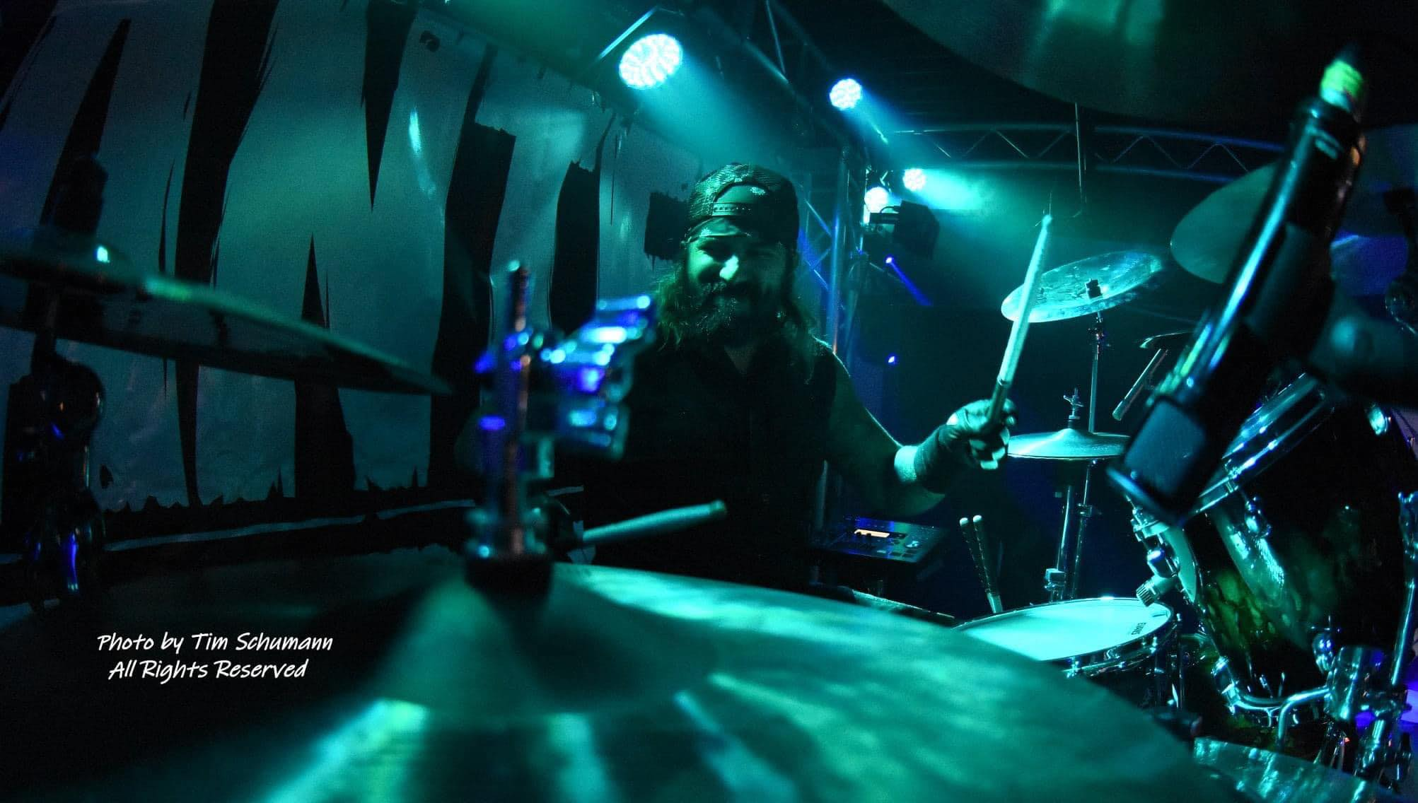 Drummer Jay Arriaga poses with Scorpion Percussion drumsticks behind his drumkit