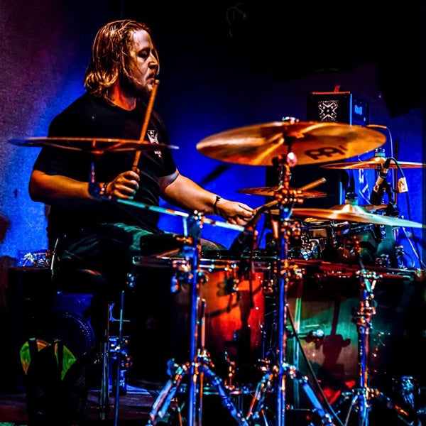 Drummer Tyler Fleming poses with Scorpion Percussion drumsticks behind his drumkit