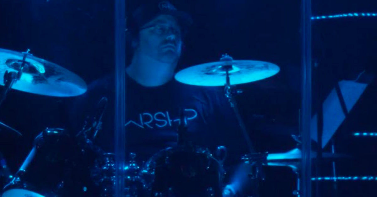 Drummer Jon Carnahan poses with Scorpion Percussion drumsticks behind his drumkit