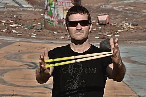 Drummer Jay Dardano poses with Scorpion Percussion drumsticks behind his drumkit