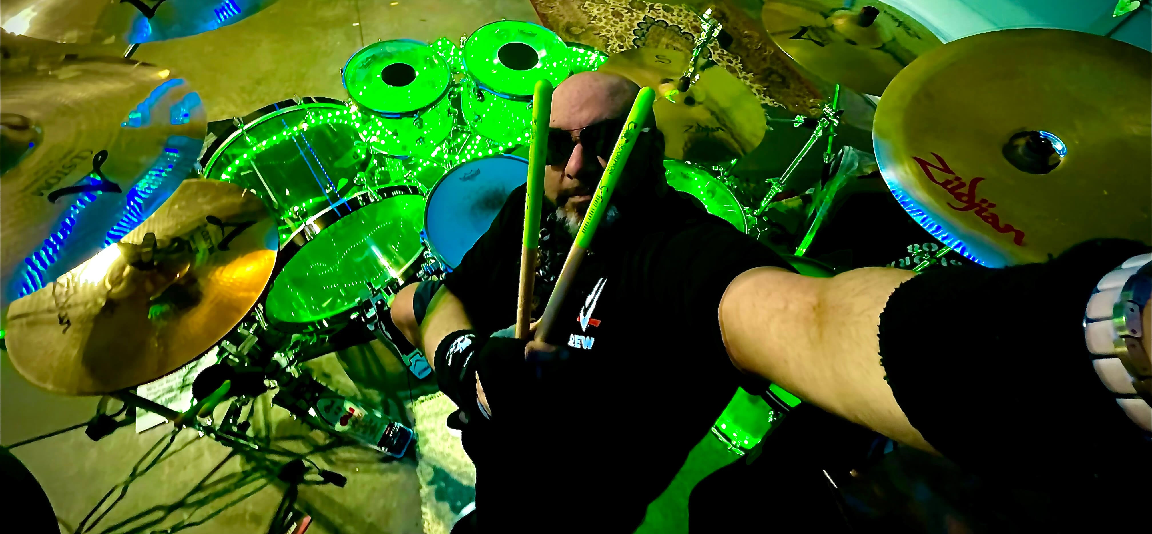 Drummer Sonny Sudra poses with Scorpion Percussion drumsticks behind his drumkit