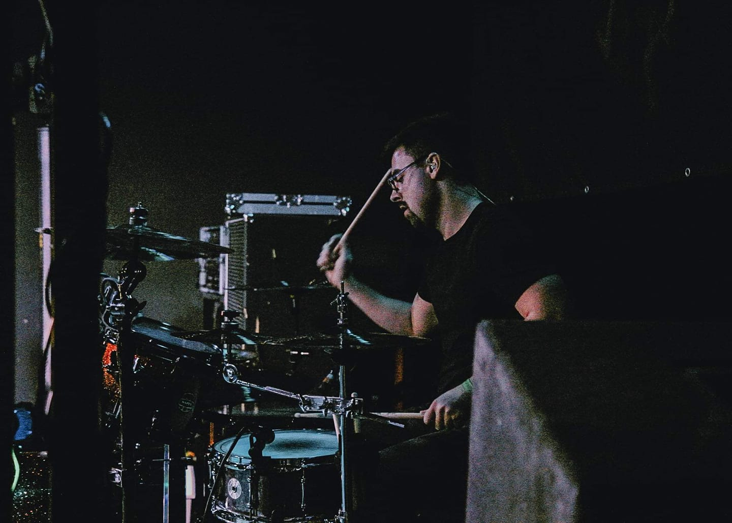 Drummer Devin Radloff poses with Scorpion Percussion drumsticks behind his drumkit