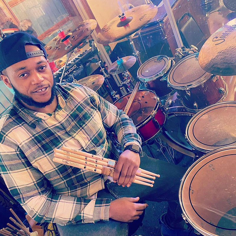 Drummer Treyvaughn Johnson poses with Scorpion Percussion drumsticks behind his drumkit