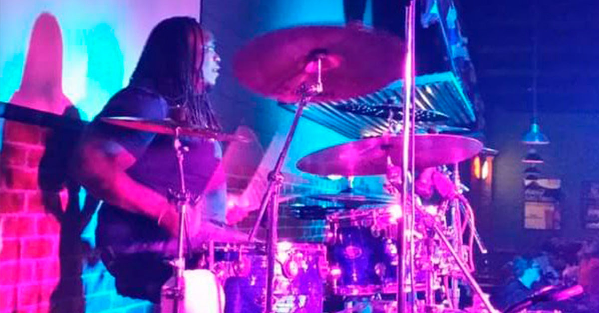 Drummer Darryl Petty poses with Scorpion Percussion drumsticks behind his drumkit